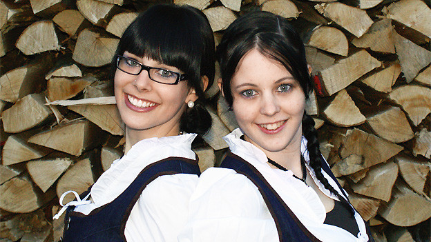 Die beiden jungen Jodlerinnen stehen vor einer Burde Holz.