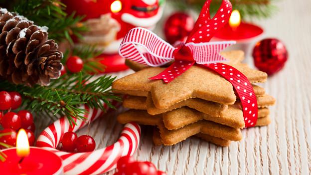 Weihnachtsdekoration mit Föhrenzapfen, Tannästen und Weihnachtsgebäck.