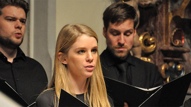 Zwei junge Sänger und eine junge blondhaarige Sängerin.