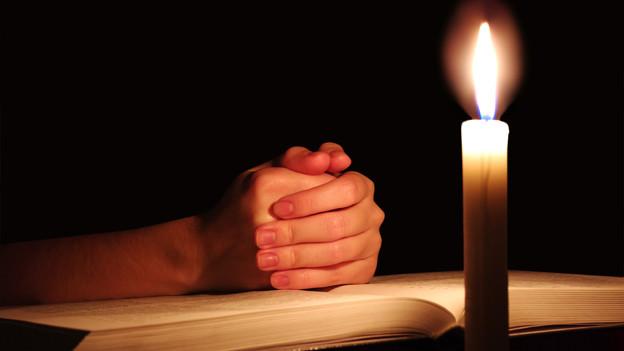 Eine aufgeschlagene Bibel, eine Kerze und betende Hände.