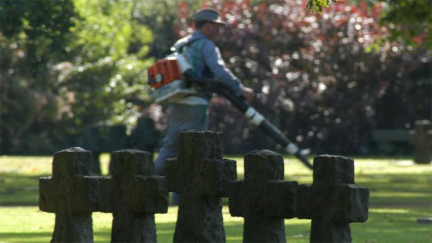 Reinigungskraft auf dem Friedhof hinter Grabsteinen.