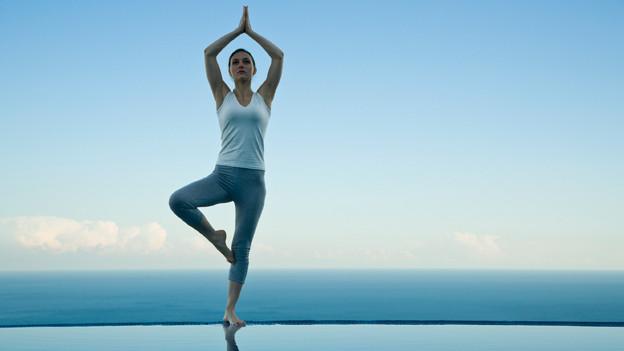Eine Frau macht am Meer Yogaübungen.