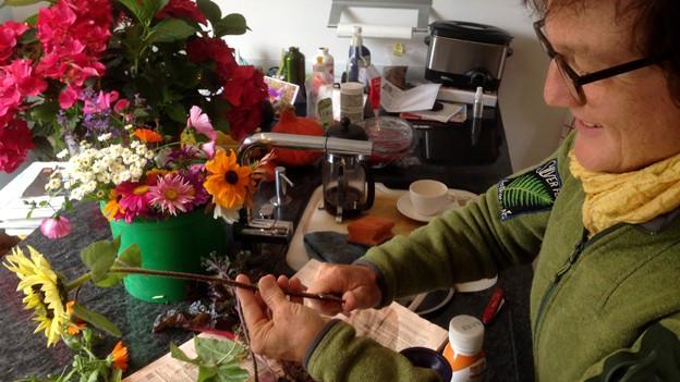 Floristin schneidet Blumen auf Tisch.
