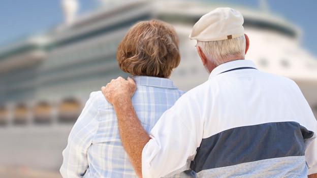 Ein Seniorenpaar. Er legt seine Hand auf ihre Schulter. Sie drehen uns den Rücken zu und betrachten ein Kreuzfahrtschiff.