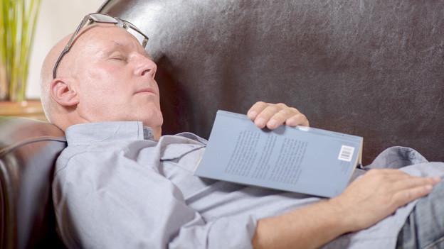 Senior schläft auf lederner Couch mit Buch auf dem Schoss.