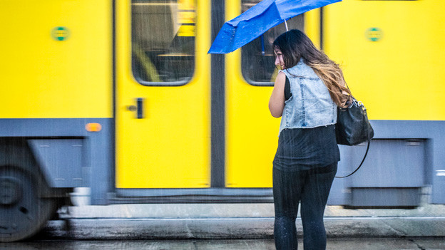Eine junge Frau steht mitten im Regen, die Strassenbahn scheint ihr vor der Nase abgefahren zu sein.