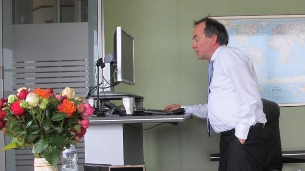 Peter Dornier stehend bei der Arbeit am Computer.