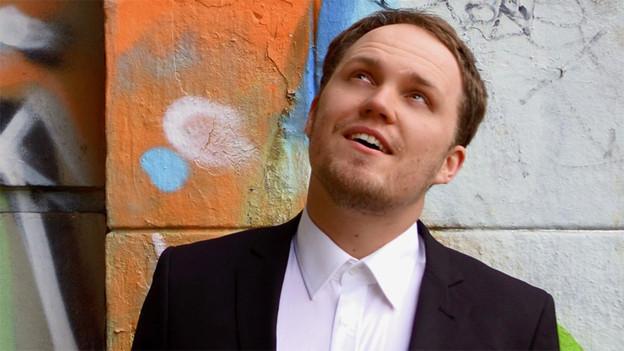 Porträt von Michael Hasenfratz vor einer bunten Mauer.