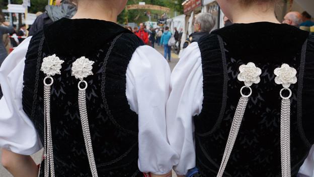 Silberschmuck auf dem Rückenteil zweier Trachten.