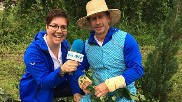 Karin Kobler interviewt Leonard, der eine Küchenschürze und einen Strohhut trägt.