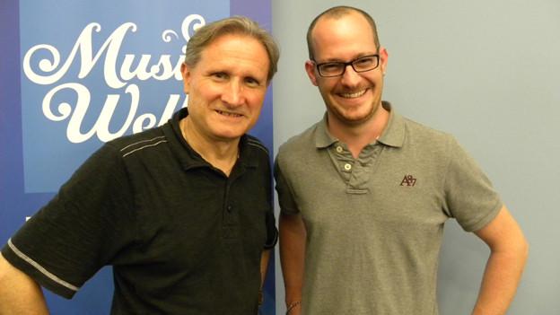 Beat Tschümperlin und Christian Schnetzer posieren vor dem blauen SRF Musikwelle-Logo.