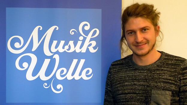 Christian Wyss posiert vor dem Logo der SRF Musikwelle.