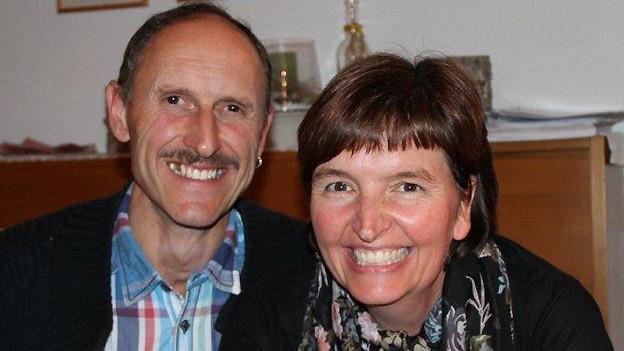 Das Ehepaar sitzt nebeneinander im Wohnzimmer.