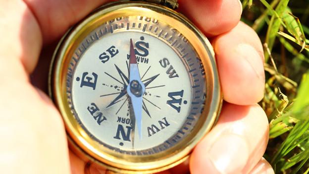 Eine Hand, die einen Kompass hält.