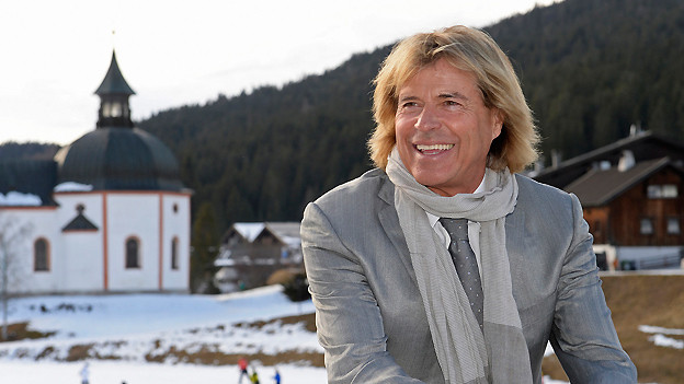 Hansi Hinterseer in einer halb verschneiten Landschaft sitzend vor einer Kapelle.