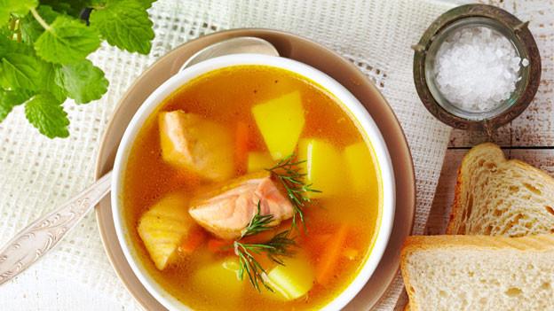 Gefüllter Suppenteller daneben ein Löffel mit Salz.