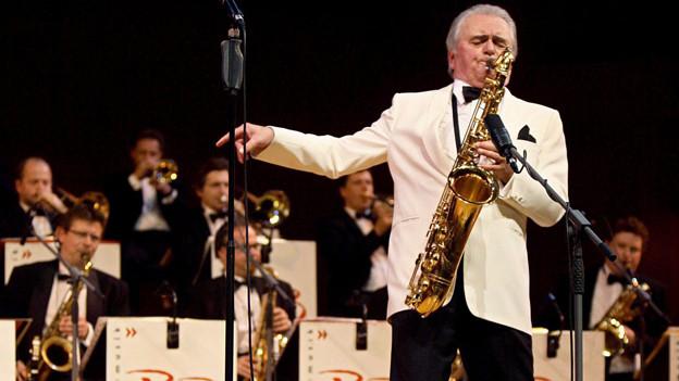 Max Greger spielt stehend Saxofon, hinter ihm sitzen die Blaser der Big Band.