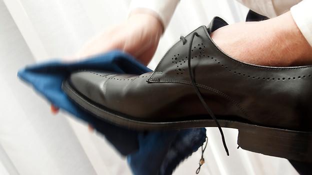Ein schwarzer Lederschuh wird mit einem blauen Lappen poliert.