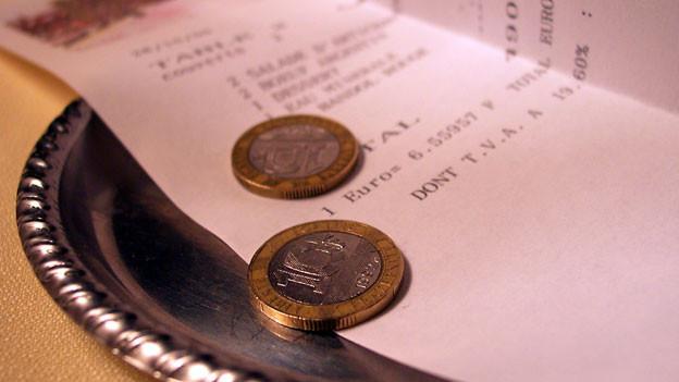 Münzen auf Tablett mit Rechnung.