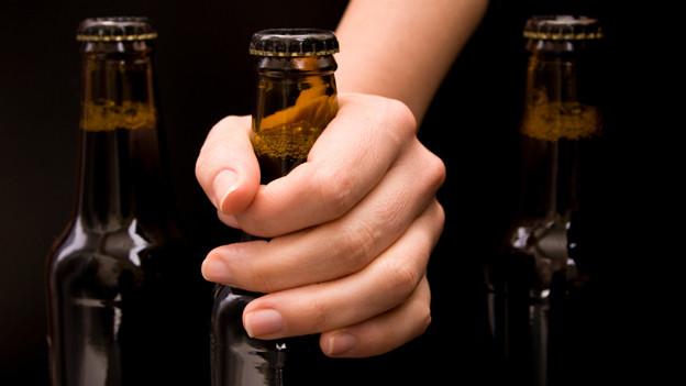 Eine Hand greift nach einer Flasche, die mit einem Kronkorken verschlossen ist.