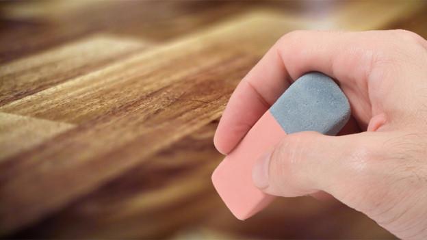 Grosse Hand mit Radiergummi über einem Parkettboden.
