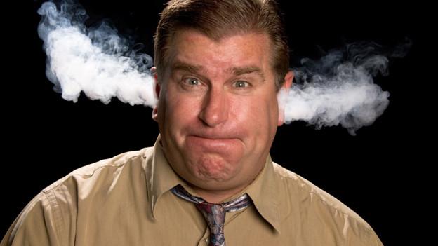 Aus den Ohren eines Mannes strömt Dampf.