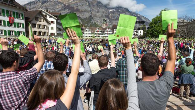 Ein Platz voller Menschen, die ihre Stimmzettel in die Höhe halten.