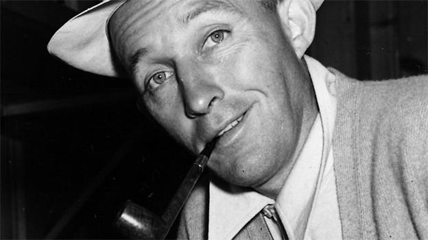 Schwarz-weiss Fotografie mit Bing Crosby, der Pfeife raucht.