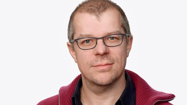 Porträt von Markus Gasser mit schwarzem Hemd und roter Strickjacke.