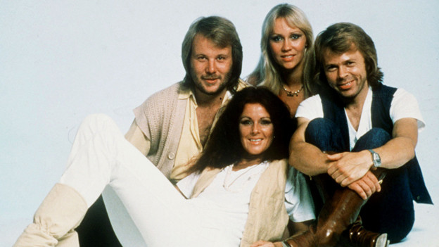 Sängerinnen und Sänger der schwedischen Gruppe ABBA posieren sitzend für ein Gruppenbild.