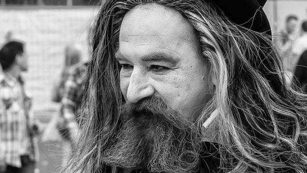 Ergrauter Mann mit zerzaustem, langem Haar und Bart.