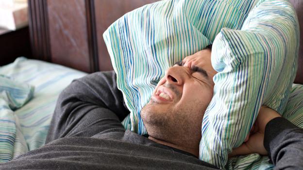 Mann liegt im Bett, drückt sich Kissen auf die Ohren um den Lärm zu dämmmen.