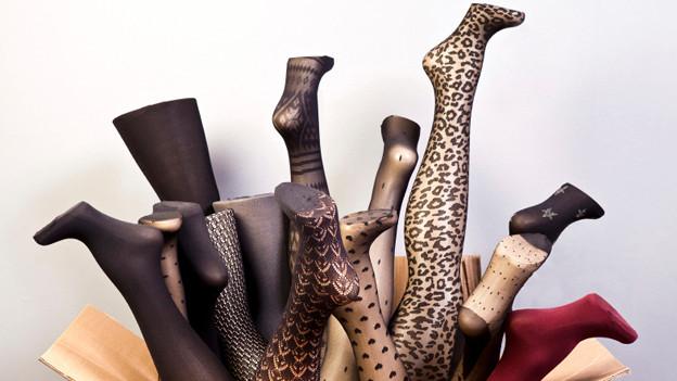 Mit Nylonstrümpfen überzogene Beine von Schaufensterpuppen in einem Pappkarton.