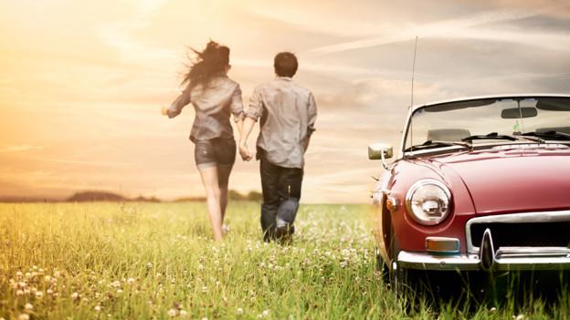 Zwei Liebende, die Hand in Hand über eine Wiese gehen. Im Vordergrund steht ein offenes Cabriolet.