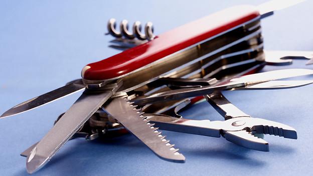 Ausgeklappte Messer und Werkzeuge eines roten Taschenmessers.