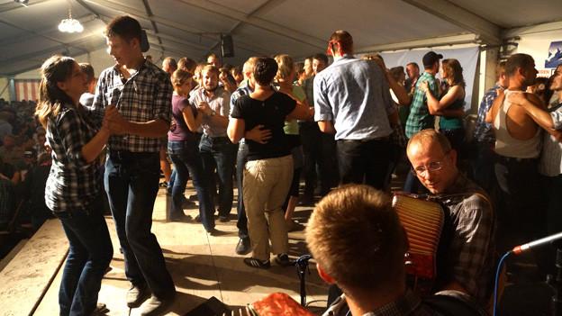 Mehrere Alphirten und Hirtinnen tanzen beim Älplerwunschkonzert.
