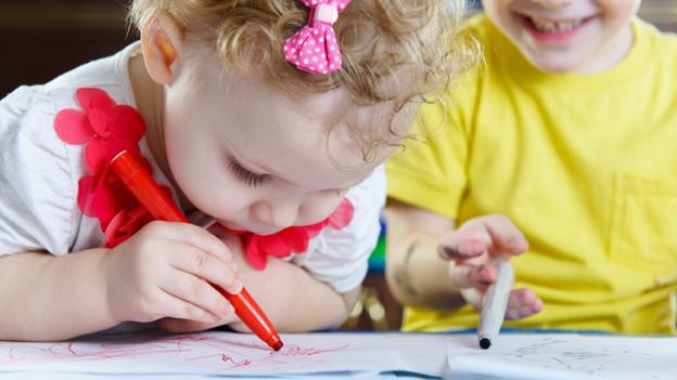 Ein Mädchen beugt sich tief über seine Zeichnung, ein anderes Kind schaut ihm zu.