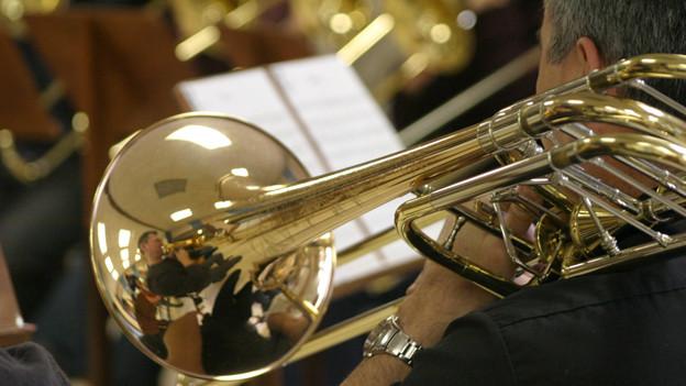Ein Mann in einem Big Band Orchester legt während einer Pause seine Trompete auf die Schulter.