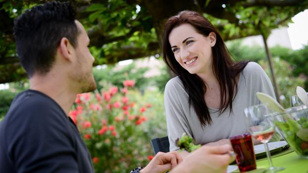 Eine Frau flirtet beim gemeinsamen Essen mit ihrem Gegenüber.