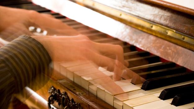 Bewegtes Bild mit Händen, die über die Klaviertasten gleiten.