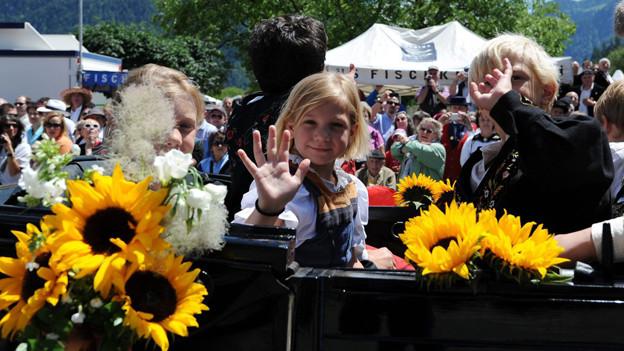 Ein Mädchen und ein Bub sitzen in ihren Trachten in einem offen Fahrzeug und winken dem Publikum zu.