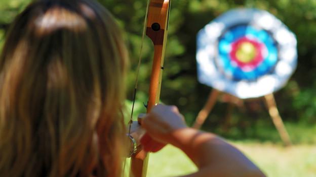 Eine Frau zielt mit der Armbrust auf eine Zielscheibe.