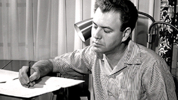 Nelson Riddle sitzt am Piano und h hält seine Ideen mit einem Kugelschreiber auf einer Skizze fest.