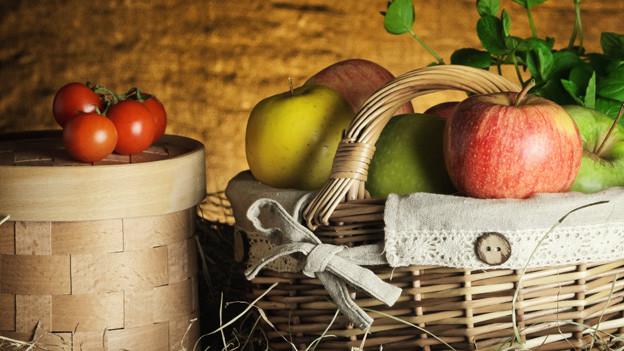Korb mit Äpfeln, daneben Korb mit Tomaten.