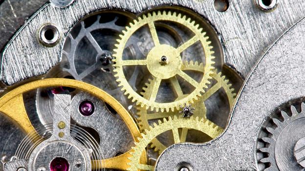 Kleine und grosse Zahnräder eines Uhrwerks.