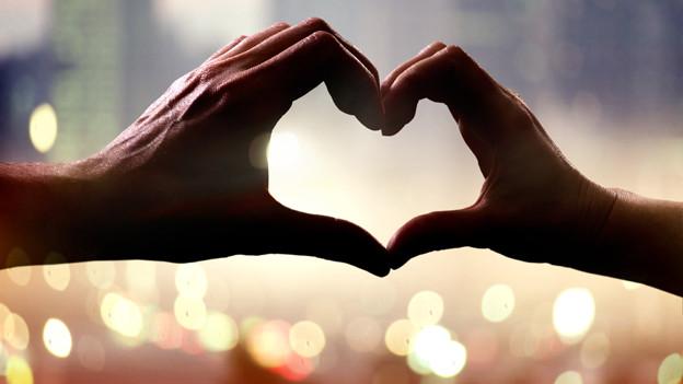 Zwei Hände, die mit den Fingern ein Herz formen.