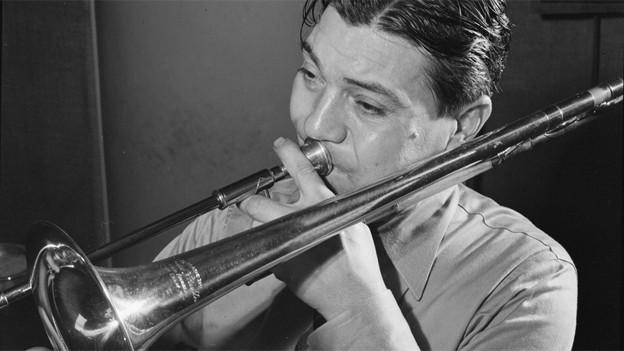 Schwarz-Weiss Fotografie von Jack Teagarden beim Posaune spielen.