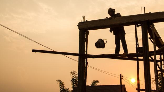 Ein Bauarbeiter auf einem Holzgerüst bei Sonnenuntergang.