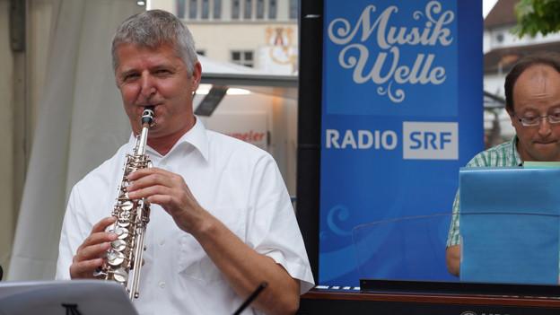 Der Musiker in weissem Hemd spielt auf der Bühne Klarinette.