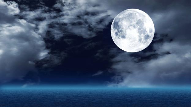 Der runde Vollmond umgeben von leichten Wolken über dem offenen Meer.
